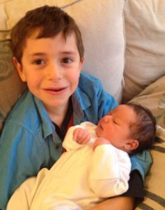 photo of boy holding new baby brother