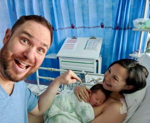 Happy dad with new mum and baby